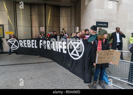 London, UK. 21st December 2018. Climate campaigners from Extinction Rebellion protest at the BBC holding a banner 'Rebel For Life'. The call on the BBC to stop ignoring the climate emergency & mass extinctions taking place and promoting destructive high-carbon living through programmes such as Top Gear and those on fashion, travel, makeovers etc. The protest, organised by the Climate Media Coalition (CMC) and its director Donnachadh McCarthy brought mannequins wrapped in white cloth to the BBC representing the bodies of a Greek village killed by fire. Peter Marshall/Alamy Live News - Stock Image