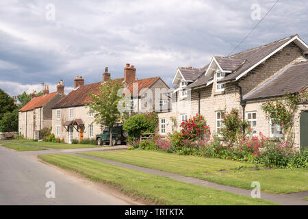 A row of stone houses and cottages along Railway Street in Slingsby, North Yorkshire, England, UK - Stock Image