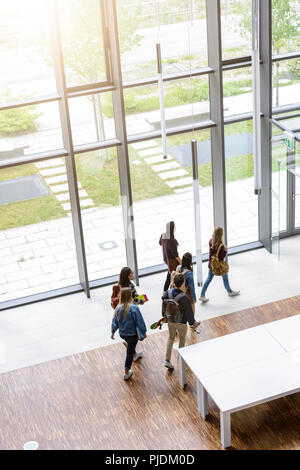 Male and female university students departing in university lobby, high angle view - Stock Image