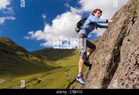 Female rock scrambler climbing up Seathwaite Slabs, Lake District, UK. - Stock Image