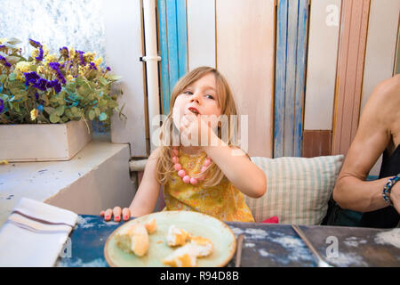 Three years old blonde little girl with yellow dress an necklace eating bread with hand, sitting indoor in restaurant next to woman - Stock Image