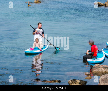 Dunbar, East Lothian, Scotland, UK. 21st Apr 2019. UK Weather:  People enjoy the very sunny hot Easter day weather at Eye Cave cove. A father and child paddle boarding - Stock Image