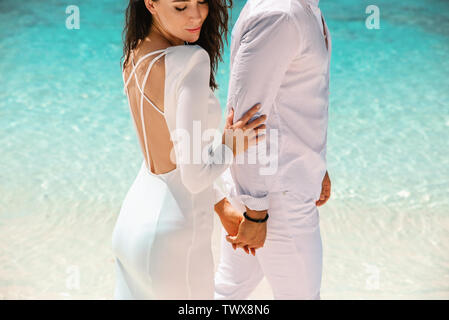Young, elegant couple enjoying the romantic moment on a beach - Stock Image