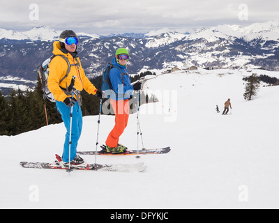 Two male skiers skiing in flat light on red run Marmotte in Le Grand Massif ski area of French Alps above Samoëns resort, France - Stock Image