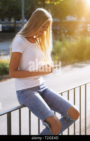 urban teenage girl using her smartphone or mobile phone while sitting on railing by city street - candid real people technology concept - backlight wi - Stock Image