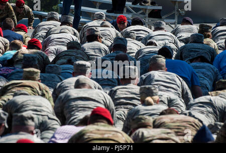 Attendees participate in memorial push-ups during Tech. Sgt. John Chapman's name unveiling ceremony at the Air Force Memorial, in Arlington, Va., Aug. 24, 2018. Chapman was posthumously awarded the Medal of Honor for actions on Takur Ghar mountain in Afghanistan on March 4, 2002. An elite special operations team was ambushed by the enemy and came under heavy fire from multiple directions. Chapman immediately charged an enemy bunker through high-deep snow and killed all enemy occupants. Courageously moving from cover to assault a second machine gun bunker, he was injured by enemy fire. Despite  - Stock Image