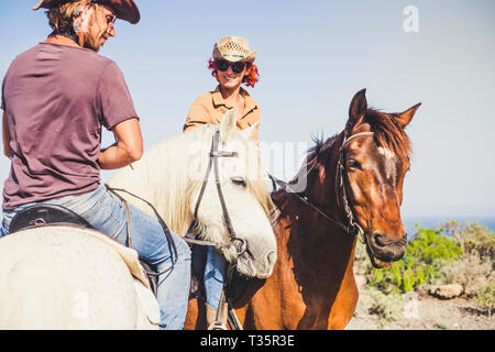 Happy smiling couple doing a horse riding togethe rin the nature - outdoor leisure activity for young people together in friendship with animals for t - Stock Image