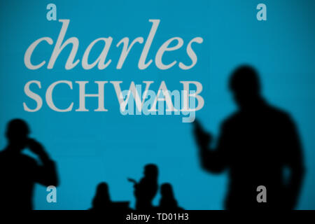 The Charles Schwab logo is seen on an LED screen in the background while a silhouetted person uses a smartphone in the foreground (Editorial use only) - Stock Image