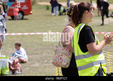 Young woman marshal in hiviz at the end of a mud run - Stock Image