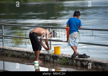 Two young, indigenous, ethnic Itza Maya boys fishing on Lake Peten, Guatemala. - Stock Image