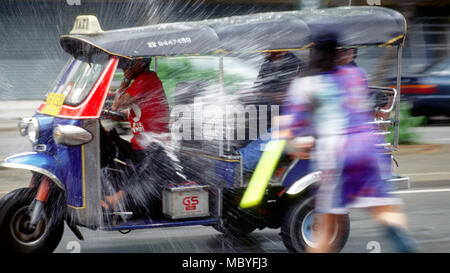 A taxi is splashed with water during Songkran, 2001 in Bangkok, Thailand. - Stock Image