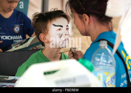 Bristol, UK. 28th July 2018.  A boy gets his face painted at todays Bristol Upfest. The festival is Europe's largest, free, street art and graffiti festival. Talented artists travel from 70 countries and across the UK to paint live on 60,000sqft of surfaces in front of 50,000 visitors over this weekend. Credit: Stephen Hyde/Alamy Live News - Stock Image