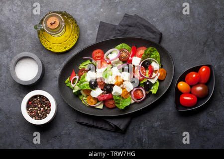 Greek salad with cucumber, tomato, pepper, lettuce, onion, feta cheese and olives, dressed with olive oil. Top view - Stock Image