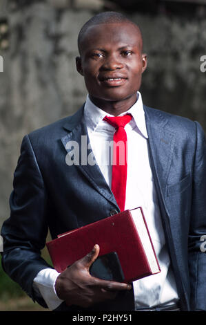 young businessman holding a book and standing outside. - Stock Image