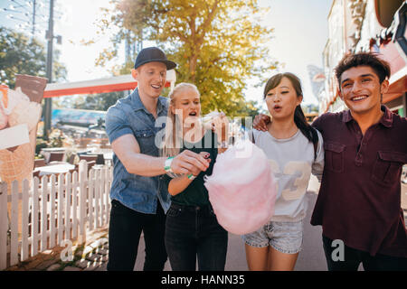 Group of friends eating cotton candy in amusement park. Young man and women sharing cotton candy floss at fairground. - Stock Image