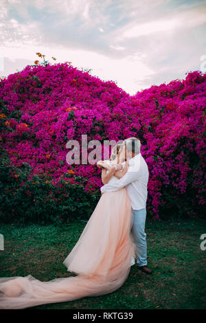 Happy newlyweds kiss among blooming trees and flowers during the honeymoon in Egypt. - Stock Image