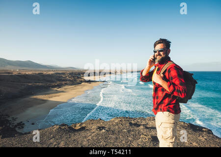 Standing caucasian man calling at the phone on a isolate cliff with ocean waves view - backpacker alternative lifestyle vacation for people love natur - Stock Image