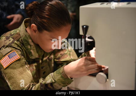 U.S. Army Spc. Natasha Crague, Joint Base Langely-Eustis MEDDAC optical laboratory specialist, moves new glasses lenses through the beginning stages of fabricating a pair of corrective lenses in support of Innovative Readiness Training Ola de Esperanza Sanadora Sept. 2, 2018, in Guaynabo, Puerto Rico. The purpose of the IRT is to provide medical, dental and optometry care to assist local municipal authorities in addressing underserved community health and civic needs while performing joint military humanitarian operations. (U.S. Air National Guard photo by 1st Lt. Francine St Laurent) - Stock Image