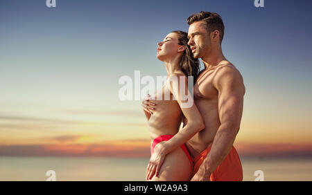 Young, relaxed couple looking at the beautiful sunset - Stock Image