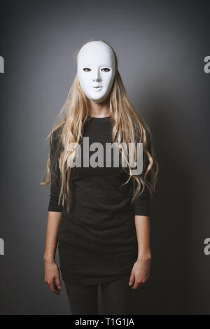 mysterious woman hiding face and identity behind plain white mask - Stock Image