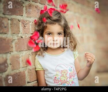 Girl, 3 years old, leans against a wall under flowers, Portrait, Germany - Stock Image