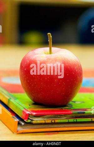 Red apple on a stack of two books in a classroom setting - Stock Image