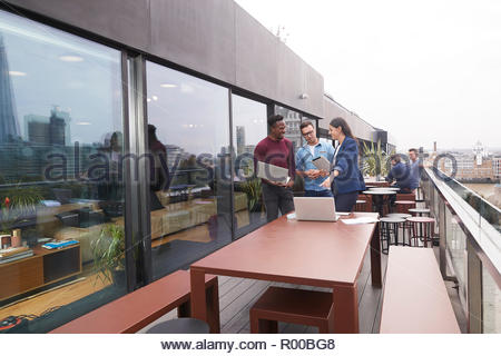 Colleagues using laptops on balcony - Stock Image