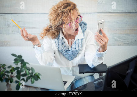 Stressed business woman shout at the phone call - two laptop on the desk and technology everywhere to work - workstation with female people - modern j - Stock Image