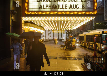 Chicago, United States. 14th Jun,  2017. Commuters outside the Chicago Theatre rush to get home in the rain storm - Stock Image
