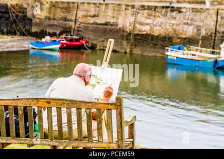 Older man painting by the fishing harbour at Craster, Northumberland, UK. - Stock Image