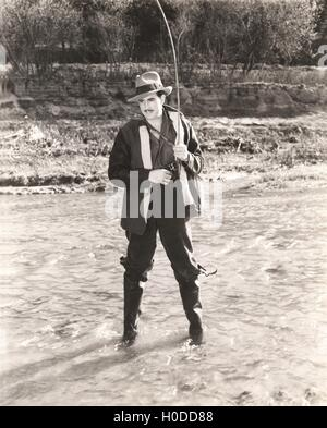 Fisherman in waders fishing in river - Stock Image
