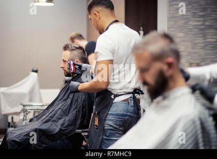 Two man clients visiting haidresser and hairstylist in barber shop. - Stock Image