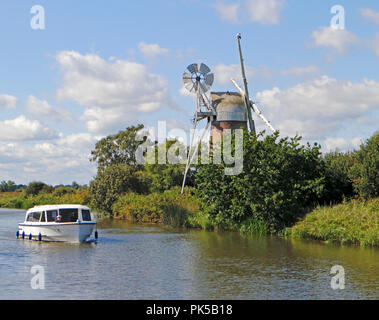 A motor cruiser passing Turf Fen Drainage Mill on the River Ant on the Norfolk Broads by How Hill, Ludham, Norfolk, England, United Kingdom, Europe. - Stock Image