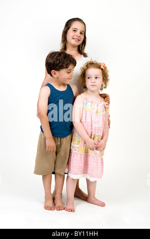 three kids posing to camera isolated on white - Stock Image