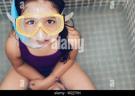portrait of a serious beautiful little girl having fun with snorkel goggles sitting in the tub while taking a bath in the bathtub, kids hygiene concep - Stock Image