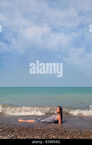 a girl lying in a lake in the waves - Stock Image