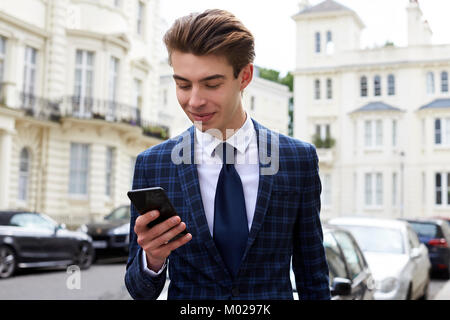 Smiling man in suit looking down at his smartphone in street - Stock Image