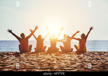 Group of five happy people sits on background of empty sunset beach. Travel or sea vacations concept - Stock Image