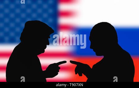 Silhouettes to represent the USA President, Donald Trump, and the Russian President, Vladimir Putin, facing each other pointing, as if arguing. - Stock Image