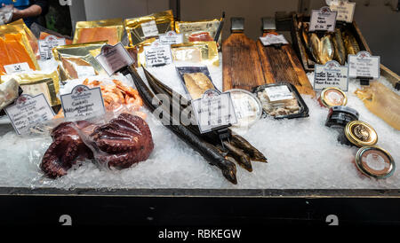Shellseekers stall at Borough Market, London, in December. Smoked eel, cooked Mediterranean Octopus, smoked mackerel, fish roe in jars, smoked fish in - Stock Image