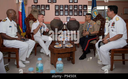 180709-N-OU129-043 SAN FERNANDO CITY, Philippines (July 9, 2018) Rear Adm. Joey Tynch, Commander, Task Force 73 (center-left) and Capt. Lex Walker, Commodore, Destroyer Squadron 7 (left), participate in an office call with Philippine Lt. Gen. Emmanuel Salamat, Commander, Northern Luzon Command (center-right), and Philippine Commodore Nichols Driz, Commander, Naval Forces Northern Luzon, during Maritime Training Activity (MTA) Sama Sama 2018. The week-long engagement focuses on the full spectrum of naval capabilities and is designed to strengthen the close partnership between both navies while  - Stock Image