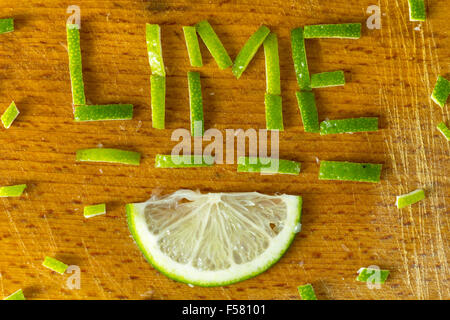 The inscription lemon lime bark on an old wooden chopping board. - Stock Image