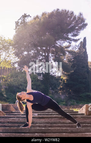 beautiful young woman doing yoga exercise on the stairs of the park, morning workout outdoors, sports and healthy lifestyle - Stock Image