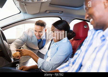 salesman showing new car to African couple in showroom - Stock Image