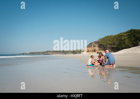 Young caucasian family with toddler child playing in the sand at a beach in Mexico - Stock Image