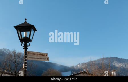 Street signs on a lamp post direct visitors to the Passionspielhaus or the Oberammergau Museum, both popular tourist attractions in Oberammergau. - Stock Image
