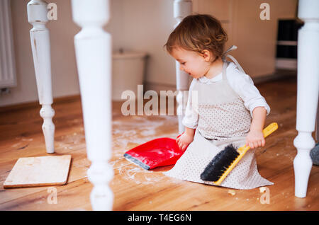 A small toddler girl with brush and dustpan sweeping messy floor in the kitchen at home. - Stock Image