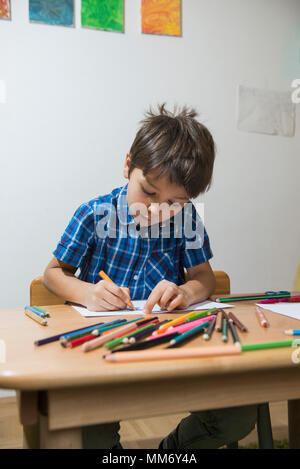 Boy coloring with colored pencils Munich, Germany - Stock Image