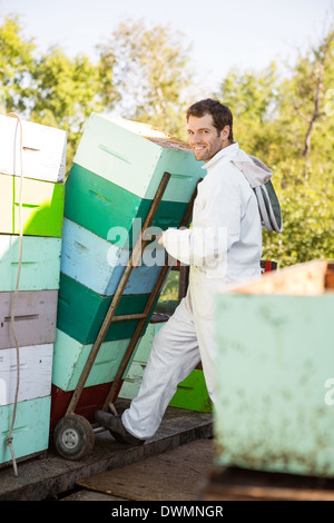 Beekeeper Smiling While Stacking Honeycomb Crates In Truck - Stock Image