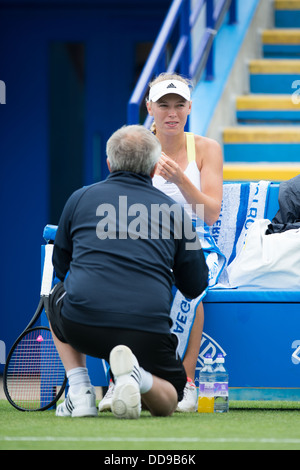 Caroline Wozniacki receives advice from her coach in a break between games during the WTA Aegon International tennis - Stock Image